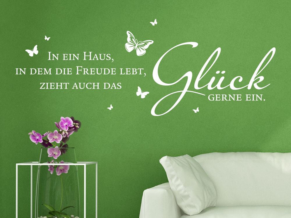 Wandtattoo Spruch Ein Haus in dem die Freude lebt auf einer grüner Wand im Wohnbereich