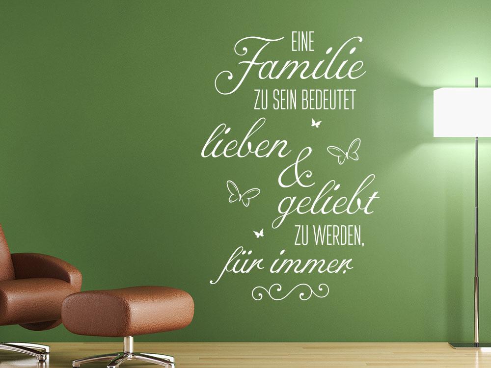 Wandtattoo Eine Familie zu sein bedeutet  lieben und geliebt zu werden auf grüner Wand in Farbe Weiß