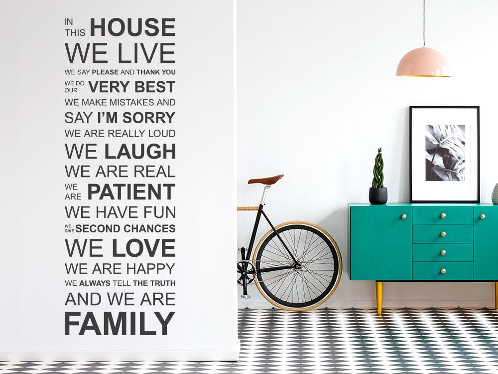 englisches Wandtattoo Spruchband In this house auf heller Wand im Flur