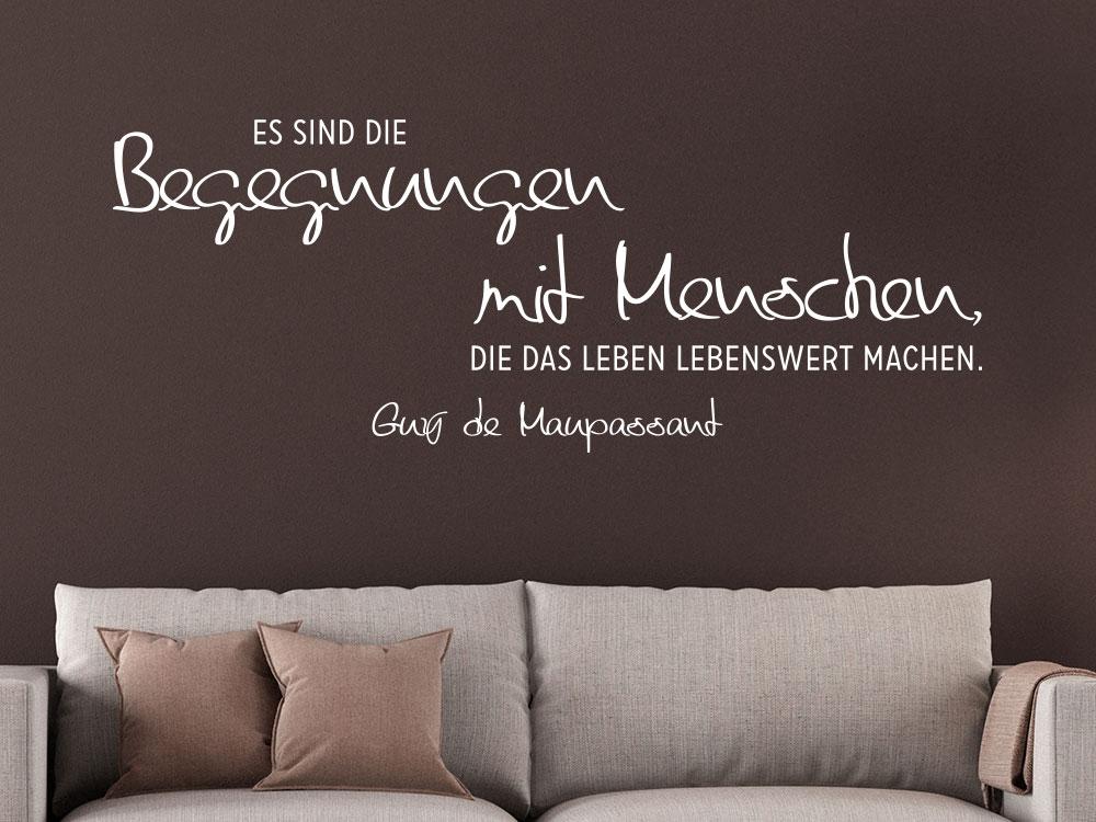 Wandtattoo Zitat Begegnungen mit Menschen... auf brauner Wohnzimmerwand