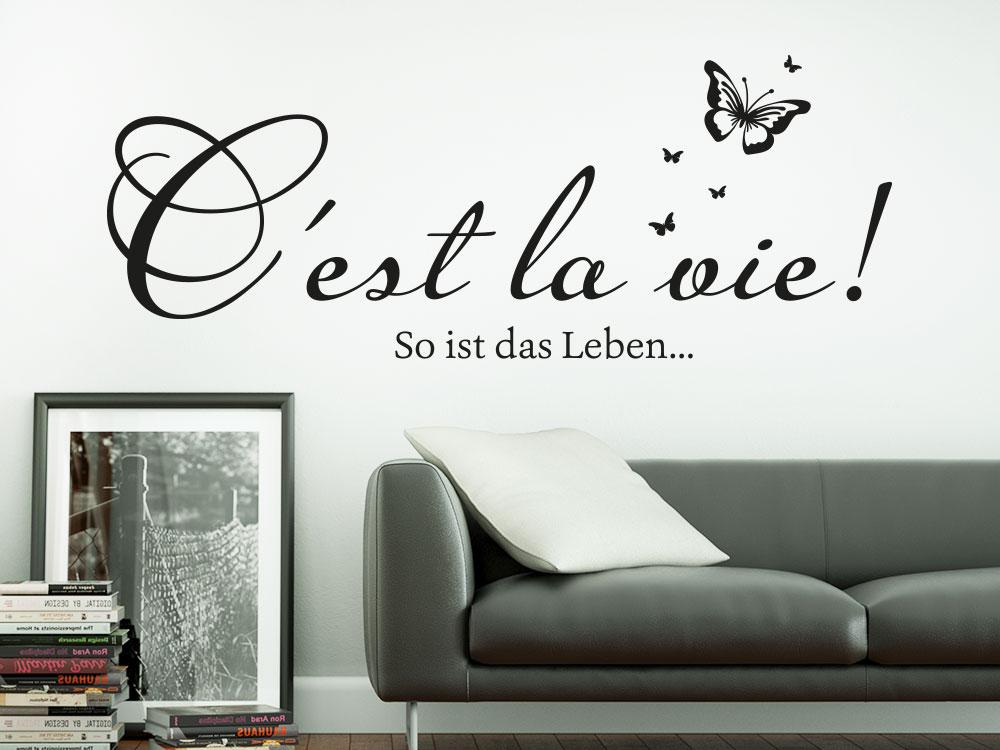 Wandtattoo C´est la vie! in Farbe schwarz über Ledersofa
