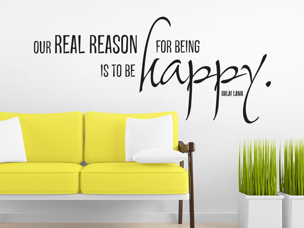 Wandtattoo Our real reason for being is to be happy In Farbe schwarz über gelbem Sofa
